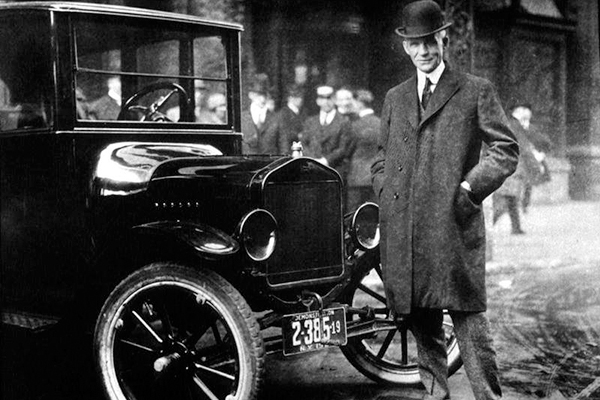 Henry Ford poses in front of a Ford